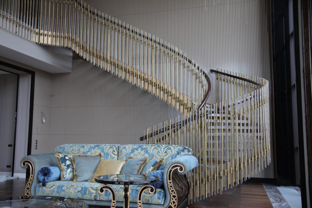 Воздушная, винтовая лестница с ограждением из латуни и стекла.